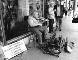 英國人的幽默:因為不值得信任的英國樂手,我自己組了一個樂器,它不吸煙也不喝酒,更不會遲到。在英國bath(巴斯)觀光區路邊看到的街頭藝人,他腳下踩著吉他,加上小提琴合奏出美妙的樂章。