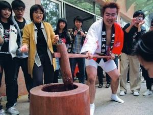 女聯會與日文系於24日在外語大樓前舉辦「日本新年文化--搗麻糬大會」,日籍生今福宏次示範如何搗麻糬,吸引百餘名師生圍觀。(攝影�劉瀚之)