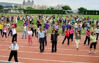 18日本校舉行日行萬步健行活動,體育名人紀政與楊傳廣蒞校,與校長張家宜及師生三百餘人在操場熱身,準備出發。(圖/記者  嘉翔)