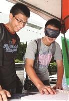 在無障礙週系列活動中,學生戴起眼罩體驗視障者閱讀點字書。(攝影/林奕宏)