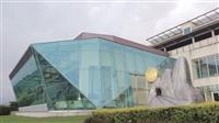 以玻璃帷幕為建築特色的強邦國際會議廳,其側之草坪上,是「蘭陽心•淡江意•雪山情」的楊英風「雪山隧道」雕塑。