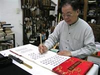 文錙藝術中心副主任張炳煌端坐並帶著戒慎緊張的心情,以羊毫正楷書寫正副總統當選證書。