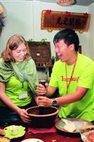 圖為來自奧地利、現就讀於國貿一的陶百合(左)及化學三鄭江帆開心合力製作擂茶。(攝影�吳佳玲)
