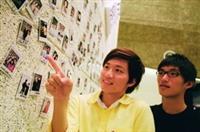 攝影成果展「我愛攝影」的這面拍立得照片牆十分熱門,引起許多同學拍照留念,競相討論照片中的人。(攝影�林奕宏)