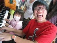 鋼琴社社員在榮民總醫院,教病童彈奏鋼琴樂開懷!(圖�課外組提供)