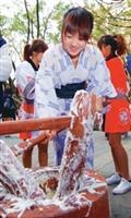 日文系學生於14日穿著日本傳統服裝示範搗麻糬,並將搗好的麻糬分送給師生享用。(圖�陳振堂攝)