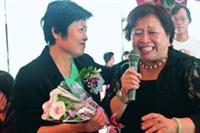 15日舉辦榮退茶會,人二組組長彭梓玲(右)為退休人員獻唱〈掌聲響起〉並獻花,因不捨而哽咽。圖左為退休人員總務處出納組編纂孫扇。(攝影�鄭雅文)