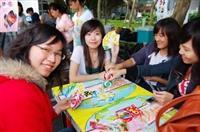 """外語週各國美食文物展,西班牙的攤位提供同學玩UNO card紙牌遊戲,當玩者手上剩餘一張牌時,必須喊出""""UNO"""",如果忘了喊,就必須再從牌堆中,抽兩張做為懲罰,圖為四位學生正在進行一場心機大戰。(文�黃士航、圖�陳振堂)"""