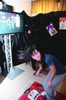 資傳系上週在商館展示廳舉行畢展,學生利用跳舞機的原理,設計出一套互動遊戲名為「地獄健檢站」,用以測試及訓練手力、腳力、柔軟度等,圖為學生開心參與遊戲的情形。(圖�王家宜)