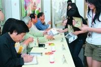 「亞洲當代繪畫聯盟展」開幕茶會上,許多師生蜂擁而至,拿著畫冊請香港畫壇大師司徒乃鍾(左一)等畫家簽名。(攝影�吳佳玲)