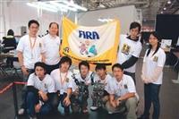 電機系師生於FIRA賽後合影,後排左二為指導教授翁慶昌,前為人形機器人。(電機系提供)