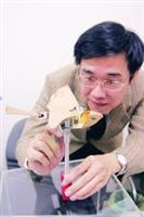 右圖為楊龍杰對「拍翼式微型飛行器」,於起飛前檢查零件。(圖�涂嘉翔)