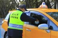 大門口管制站,計程車乘客開窗讓警衛量額溫