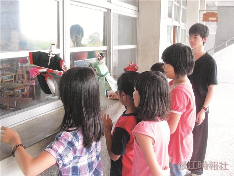淡蘭布袋戲研習社指導小朋友練習操戲偶,小朋友開心的練習。(圖片/淡蘭布袋戲研習社提供)