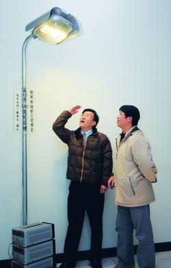 研發長康尚文(左)和機電系博士生簡坤誠,研發「以多層基板結構散熱之LED燈具」獲美專利,並實際應用於學校的路燈。(攝影�陳怡菁)