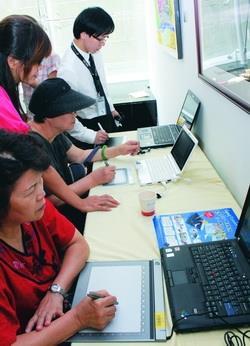 參觀「e筆書畫藝術展」者,爭相試用e筆書畫系統。(圖�曾煥元)