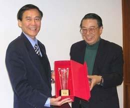 中華電信訓練所所長曹善信頒發獎座給學校,由學術副校長馮朝剛代表校長接受。