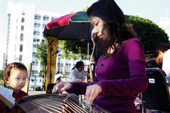 古箏社同學在海報街現場演奏,動人的樂聲連小朋友也忍不住駐足聆聽。(圖/記者陳振堂)