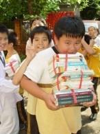 文化國小小朋友在資圖系師生帶領下,用接力把書傳進新圖書館裡,搬到手痠仍開心地笑。(資圖系游承恩提供)