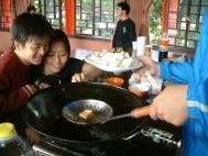 烹飪社同學在上週覺軒花園教室現場炸豆腐,香味四溢,吸引同學聞香來品嚐。(記者張佳萱攝影)