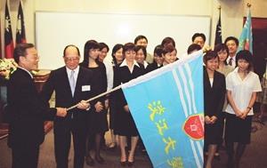 ●創辦人張建邦博士親自授旗予應日系陳山龍主任,該系此次有十五位同學即將前往日本姐妹校修習學分。