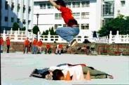溜冰表演社員驚險飛躍,地上同學嚇得蒙住眼睛。(記者陳國良攝影)