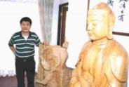 吳榮賜和他的木雕作品。(曾昱偉攝)