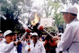 張創辦人將聖火分別引燃給主跑的校長,圖為林雲山前校長,中為張紘炬校長。