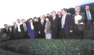 創辦人張建邦(前排中)於八十六年第二次簽約後,領當時的高教司司長黃碧端(前排右四)及前任校長林雲山、現任校長張紘炬等人至蘭陽校園視察,於茶園中合影。(董事會提供)