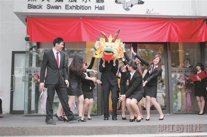 教科系畢展開幕,學生著正式服裝跳舞,伴隨吉祥物熱情邀請同學參觀。(攝影/李鎮亞)